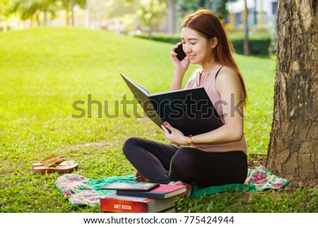 reading a book while on the phone under the tree