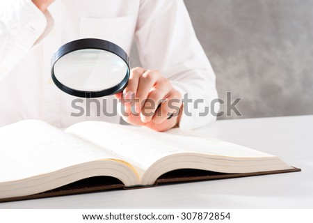 reading a book with a loupe - stock photo