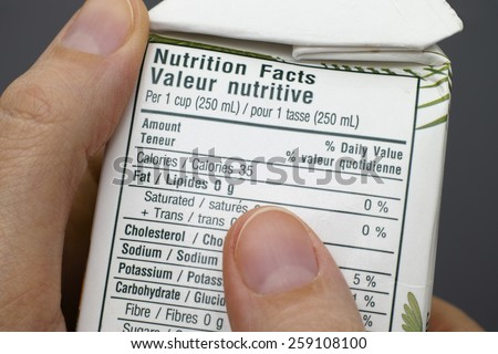 Reading a nutrition facts on box with coconut water.  - stock photo
