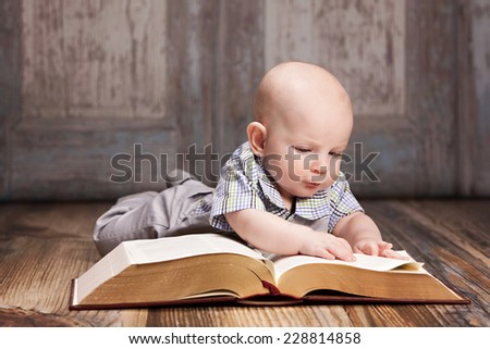 Reading.  Adorable baby boy lying on the floor reading a giant book. - stock photo