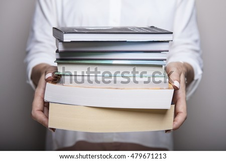 Reading and student college concept. Woman holding a pile of old books for studying. Female librarian hands.