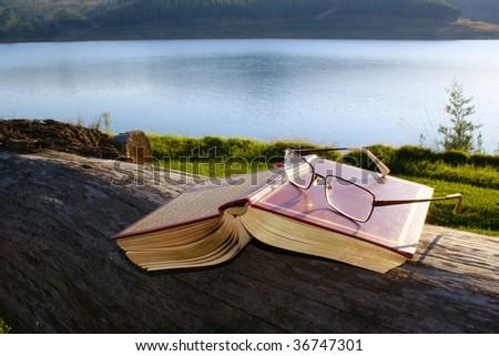 Reading at lakeside - stock photo