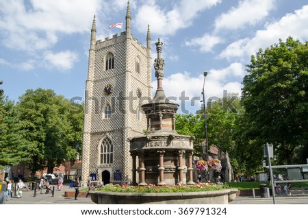 READING, BERKSHIRE - SEPTEMBER 10, 2015: Pedestrians walking in the sunshine past the historic Reading Minster church with the Queen Victoria Jubilee Fountain in the foreground. - stock photo