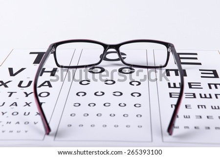 Reading black eyeglasses and eye chart close-up on a light background - stock photo