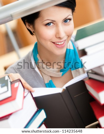Reading book female student surrounded with piles of books sitting at the desk at the library