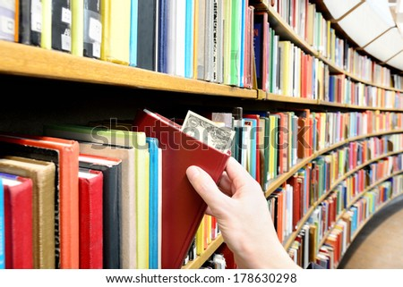 Reading/education makes you successful. Hand picking book with dollar bill in library - stock photo