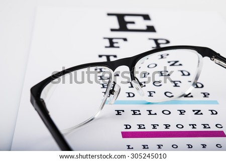 Reading eye glasses and test chart on paper