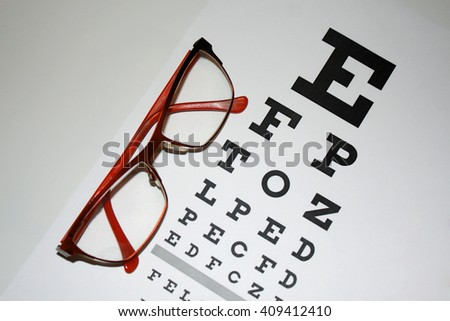 Reading - eyeglasses and eye chart close-up on a light background - stock photo