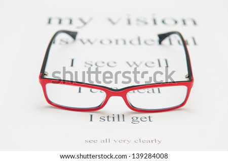 Reading eyeglasses and eye chart. close-up. on a light gray background - stock photo
