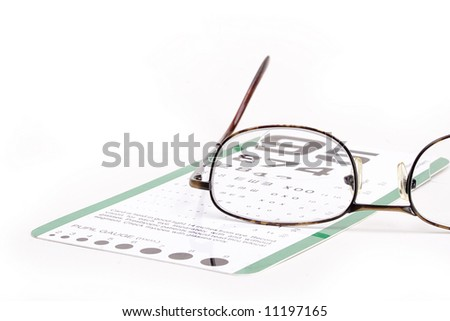 Reading eyeglasses with eye chart underneath on a white background. - stock photo