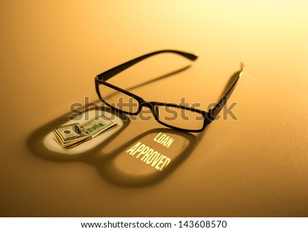 Reading eyeglasses with loan approved money - stock photo