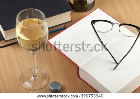 Reading glasses and a glass of wine with some books of a wooden table - stock photo