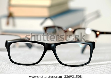 reading glasses and books on the white table, shallow depth of field
