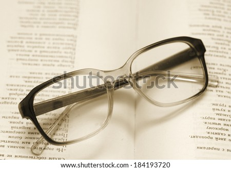 reading glasses lying on an open book - stock photo