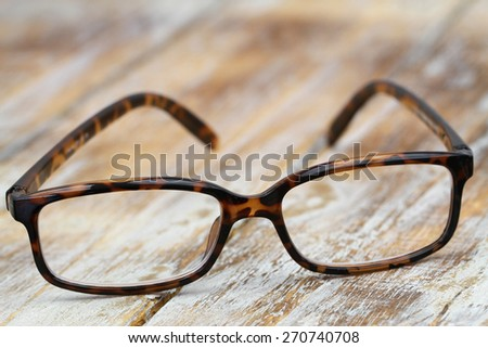 Reading glasses on rustic wooden surface