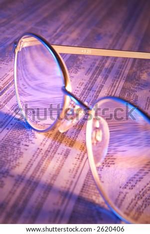Reading glasses on stock report - stock photo