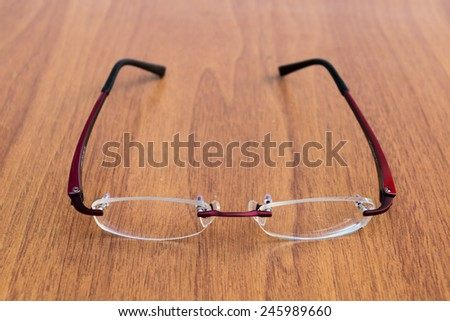 Reading glasses on the wood table - stock photo
