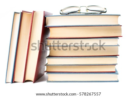 Reading glasses on top pile of books