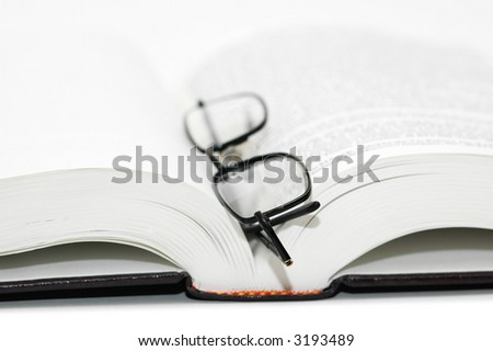 Reading glasses over the open textbook -  shallow DOF - stock photo