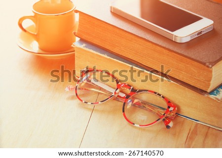 reading glasses, stack of  old books and smartphone over wooden table, retro filtered image - stock photo