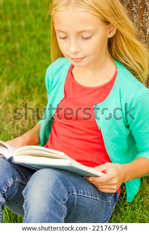 Reading her favorite book. Top view of cute little blond hair girl reading book while sitting on green grass and leaning at the tree - stock photo