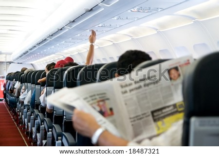Reading newspaper in a plane