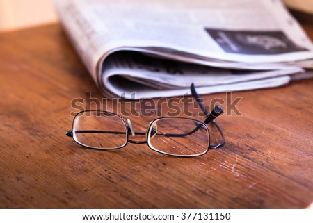 reading newspapers, glasses and daily news on wooden table - stock photo