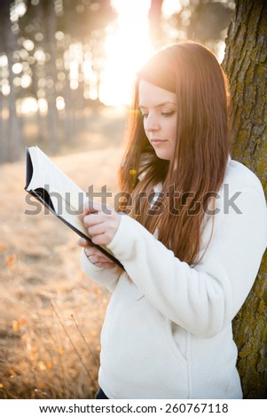 Reading Outdoors - This is an image of a beautiful young woman enjoying the nice weather and reading outside in the park.  - stock photo