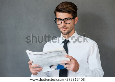Reading some business news. Confident young man in shirt and tie holding newspaper and looking at camera while standing against grey background