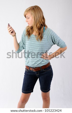 Reading Text Message. Teenage girl reading a text message on her cellphone. Note: Not Isolated. - stock photo