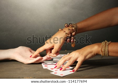 reading the lines hand and woman's hands on grey backcground - stock photo