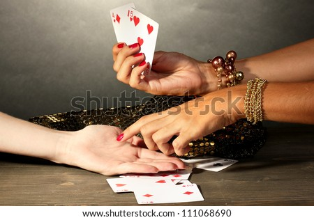 reading the lines hand in a woman's hands on grey backcground - stock photo