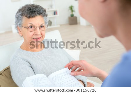 Reading to an old lady - stock photo