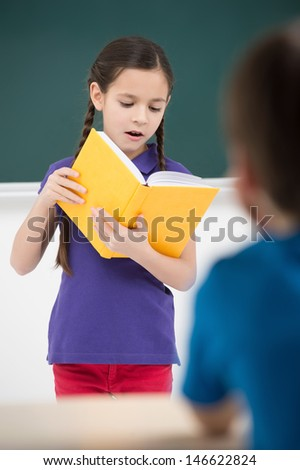 Reading to the class. Confident little schoolgirl reading a book to the classmates - stock photo