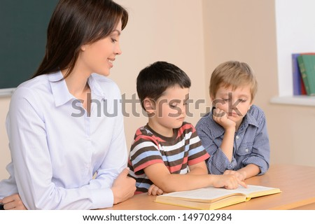 Reading together. Cheerful young female teacher sitting near two schoolboys reading a book