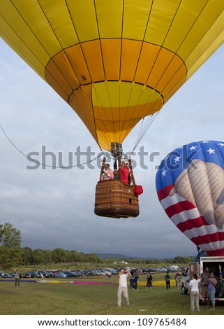 READINGTON, NJ-JUL 29:Passengers in the gondola of a hot air balloon as it begins to ascend from the launch area at the Quick Chek New Jersey Festival of Ballooning on July 29, 2012 in Readington, NJ.