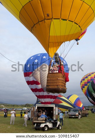 READINGTON, NJ-JUL 29: Passengers stand in the gondola of a hot air balloon as it ascends over the launch area at the Quick Chek New Jersey Festival of Ballooning on July 29, 2012 in Readington, NJ.