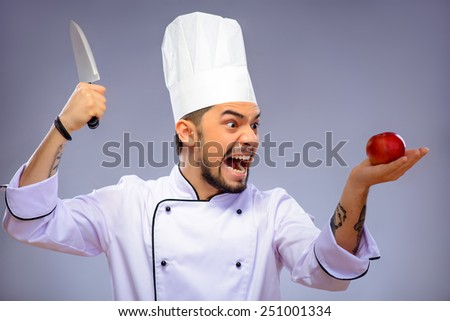 Ready for a culinary sensation. Closeup portrait of handsome funky cook in uniform holding a knife and an apple with aggressive look while standing over grey background with copy space - stock photo