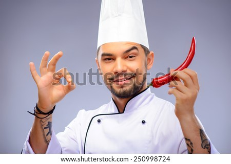 Ready for a culinary sensation. Closeup portrait of handsome funny cook holding out red pepper and showing ok sign while standing over grey background with copy space - stock photo