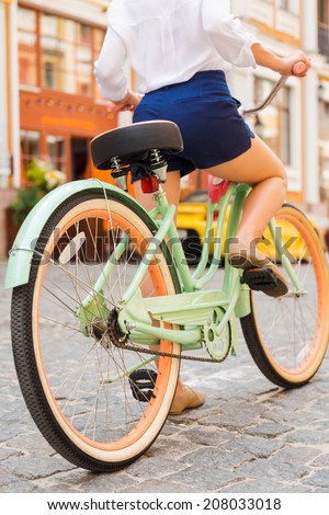 Ready for a ride. Close-up of young woman riding bicycle along the street - stock photo