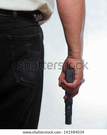 Ready for Action/Close partial image of man from behind holding automatic pistol against white background - stock photo