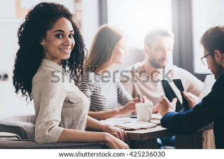 Ready for brainstorming. Beautiful cheerful African woman looking at camera with smile while sitting at the office table with her coworkers - stock photo