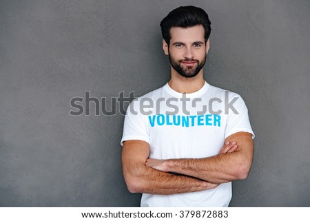 Ready for charity work. Confident young man in volunteer t-shirt keeping arms crossed and looking at camera with smile while standing against grey background