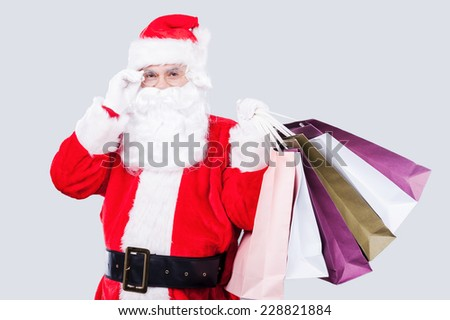 Ready for Christmas sales? Happy Santa Claus holding shopping bags and adjusting his eyeglasses while standing against grey background - stock photo