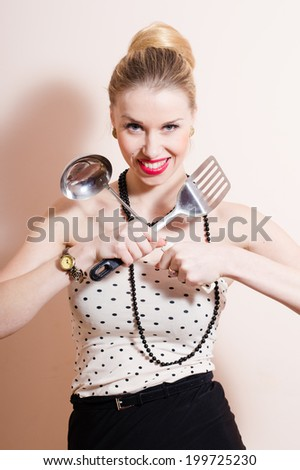 Ready for cooking with ladle & spatula: portrait of sexy pinup girl beautiful blond young woman in polka dots having fun posing happy smiling & looking at camera on white copy space background picture - stock photo