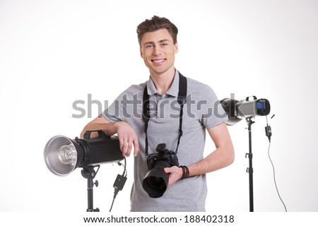 Ready for shooting. Handsome young man in polo shirt holding digital camera and smiling while standing in studio with lighting equipment on background  - stock photo