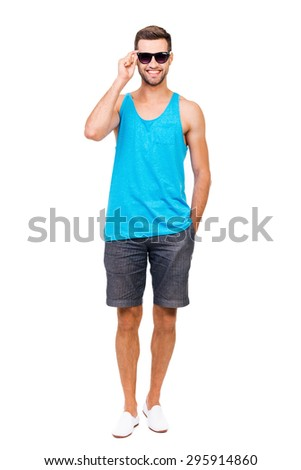 Ready for summer vacation. Full length of cheerful young man adjusting eyewear and looking at camera while standing against white background - stock photo