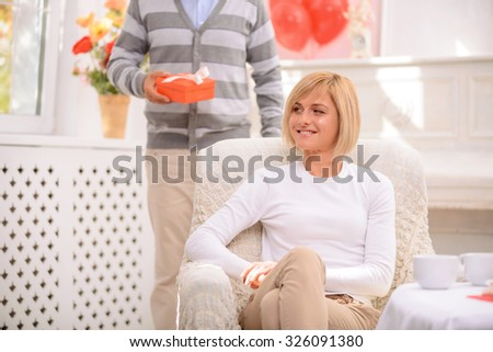 Ready for surprises. Pleasant charming upbeat woman sitting in the armchair while her husband holding present and standing on  the background - stock photo