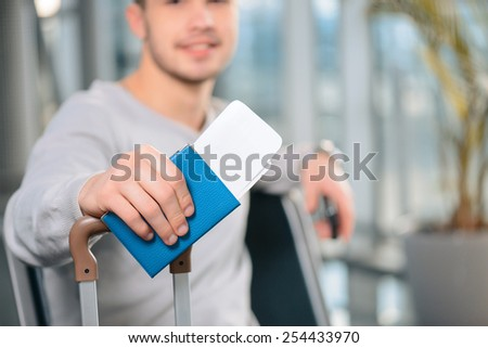 Ready for the flight. Closeup image of passport and luggage of a handsome smiling man in casual wear sitting in the hall of the airport  - stock photo