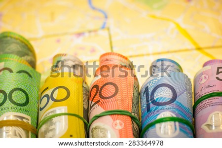 Ready for travel with colorful of Australian Dollars roll with all denomination on blurry map background - stock photo